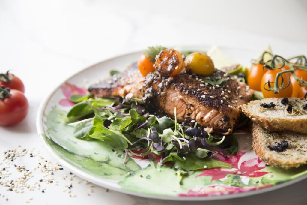 Saumon grillé sur lit de pousses et de mâches avec sa vinaigrette à l'ail noir / Cinq Fourchettes