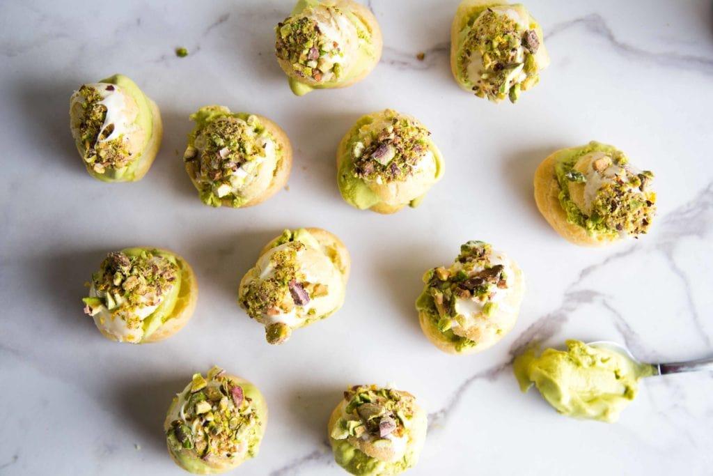 Profiteroles à la pistache avec garniture au chocolat blanc, pistaches concassées et fleur de sel / Cinq Fourchettes